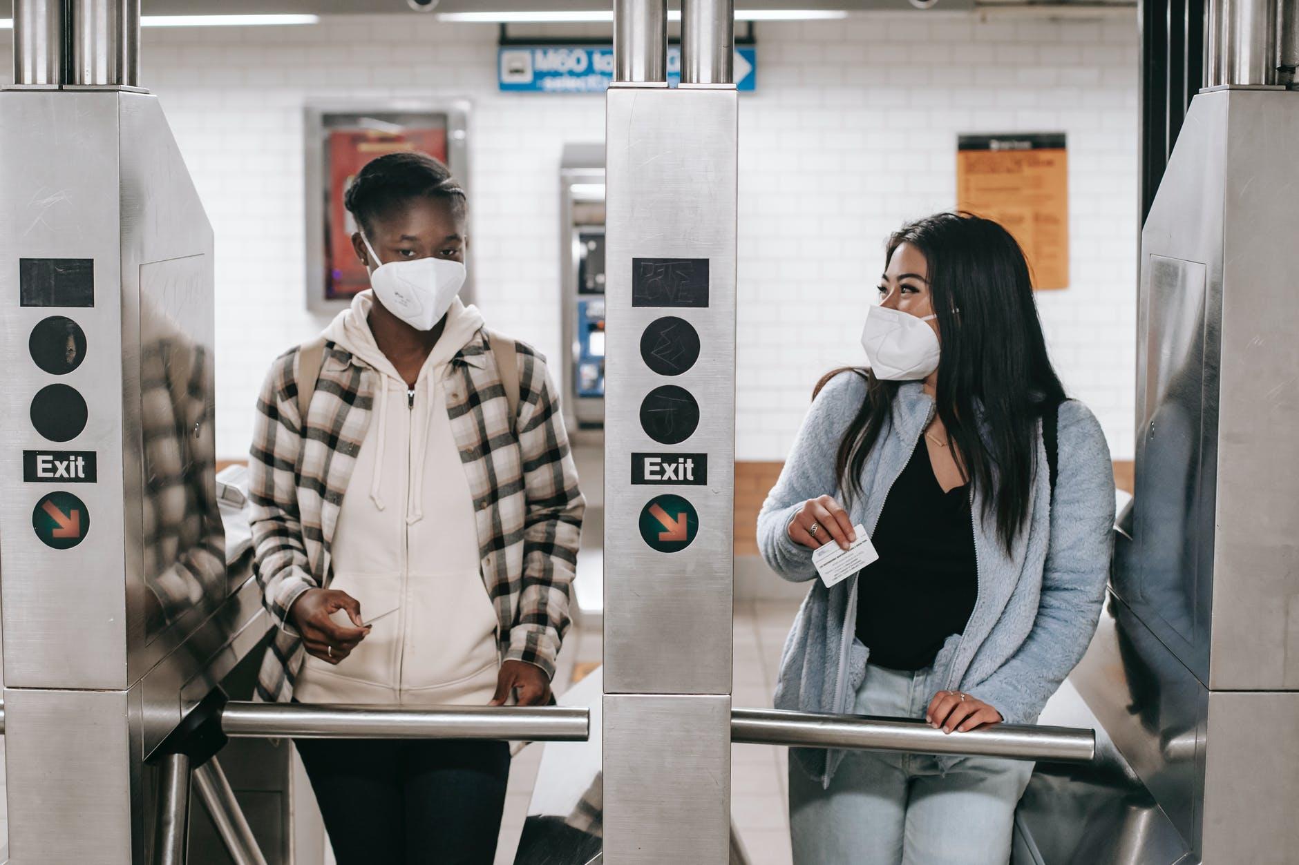 diverse women in mask entering metro